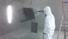 een poedercoater brengt het kleurpoeder aan op het metaal